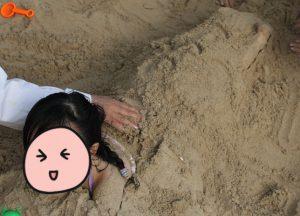 砂に埋もれる娘